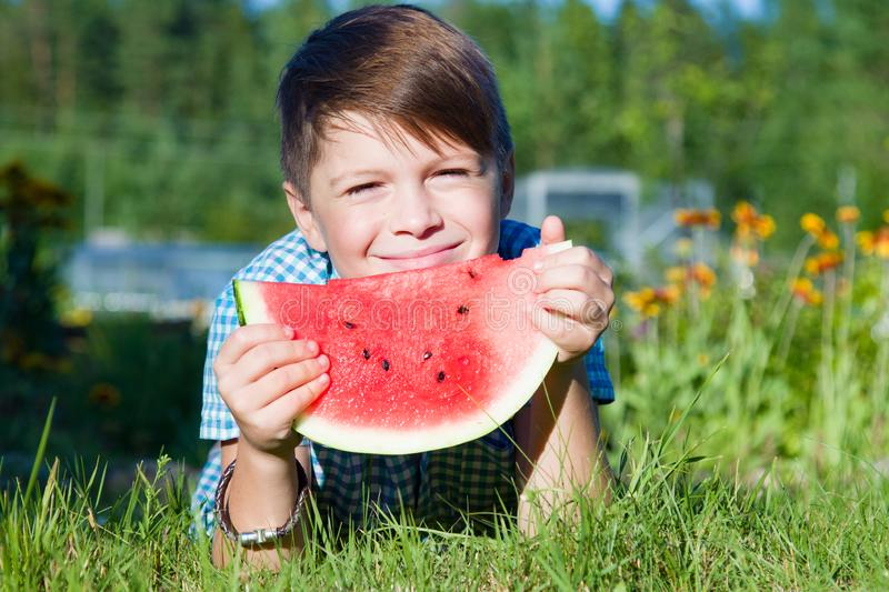 Funny boy eats watermelon outdoors in summer park stock image