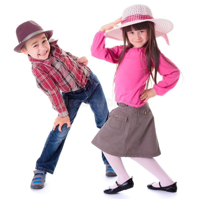 Funny boy and girl. Funny children: boy and girl wearing hats and posing in unusual posture royalty free stock photos