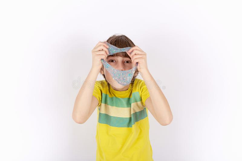 Funny boy holding slime and looking through its hole.  stock photo