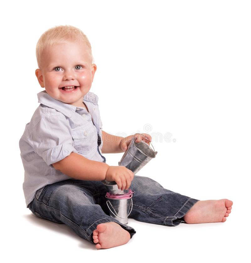 Funny boy holds small toys buckets in his hands. Isolated on white background royalty free stock images