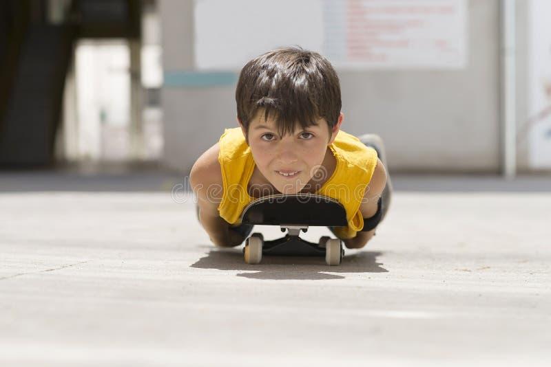 A Funny boy lying on a skateboard. Funny boy lying on a skateboard looking to camera stock photos