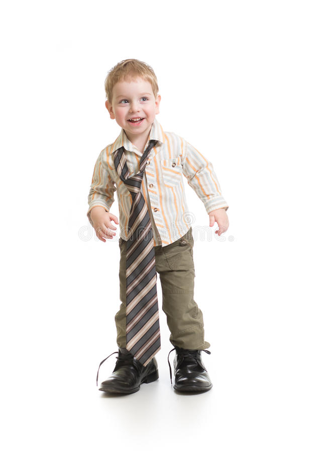 Funny boy playing in big father's shoes isolated. On white stock images