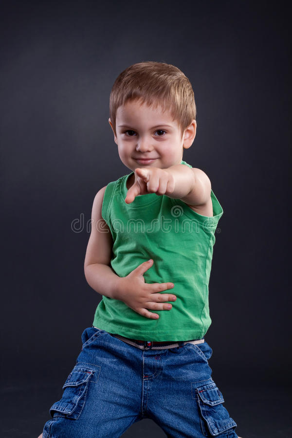 Funny boy pointing. The finger a over dark background royalty free stock images