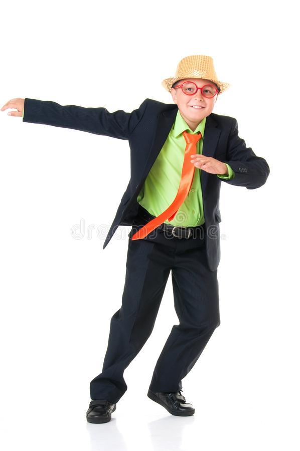 Funny boy schoolboy in a business suit, bright tie and funny glasses and a hat emotionally dancing on an isolated white background stock images