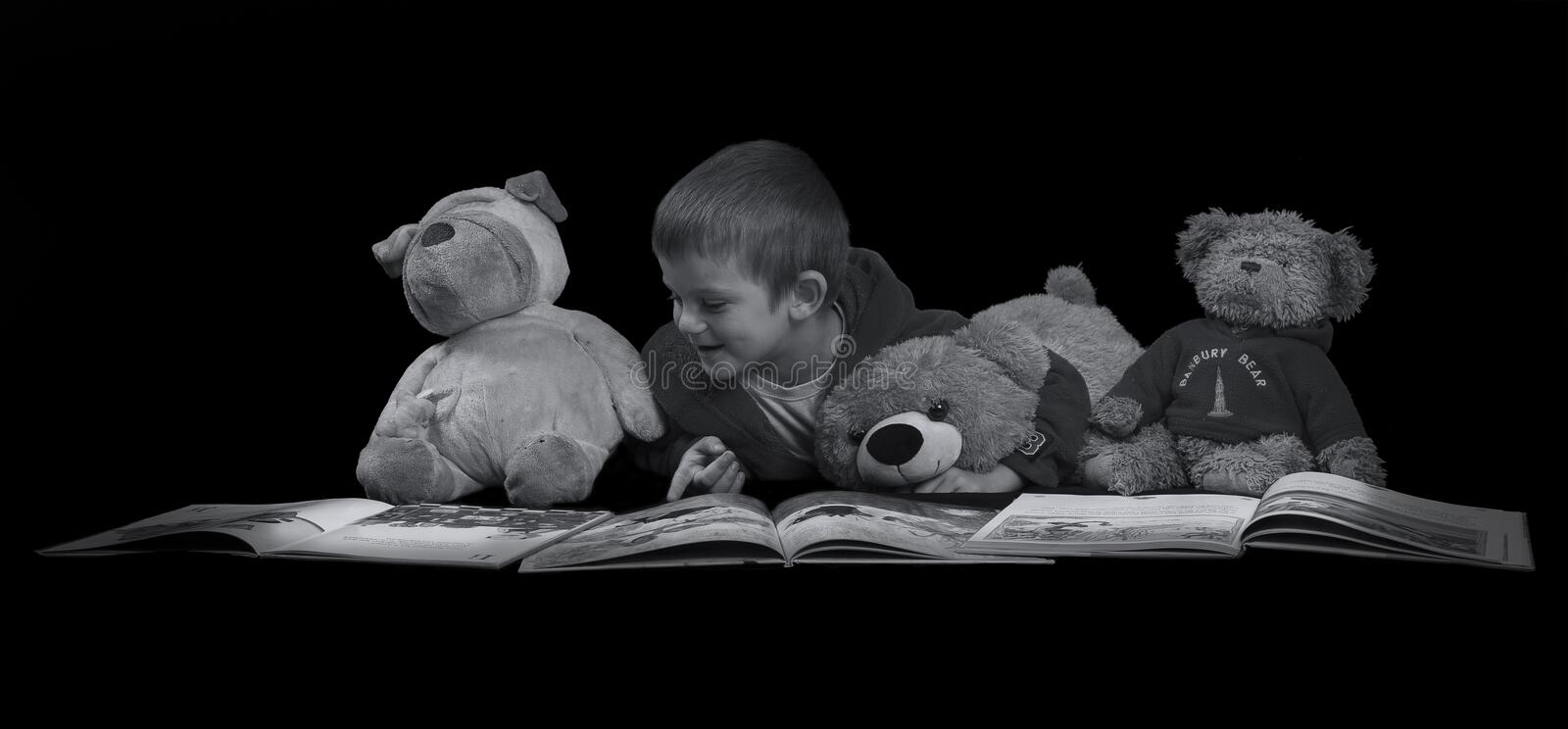 Funny boy with stuffed animals reading a book before bed time ar. Funny boy with many stuffed animals reading a book before bed time artistic conversion royalty free stock photo