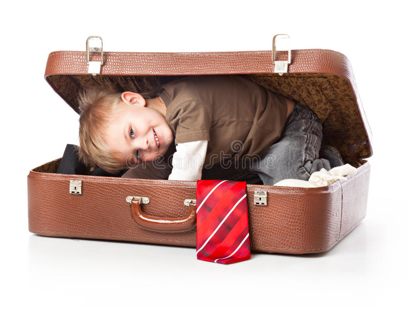 A funny boy in a suitcase. Isolated on a white background royalty free stock photo