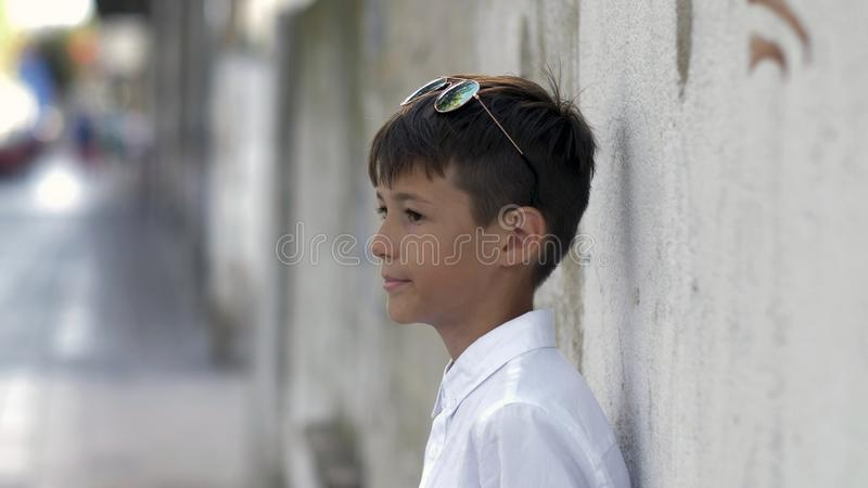 Funny boy in sunglasses waiting for someone, leaning against the wall in the city and looking at people. Have fun stock photos