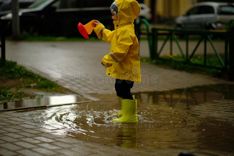 Happy child is playing in a puddle on a summer rainy day. a boy in a yellow raincoat walks in the park. royalty free stock images