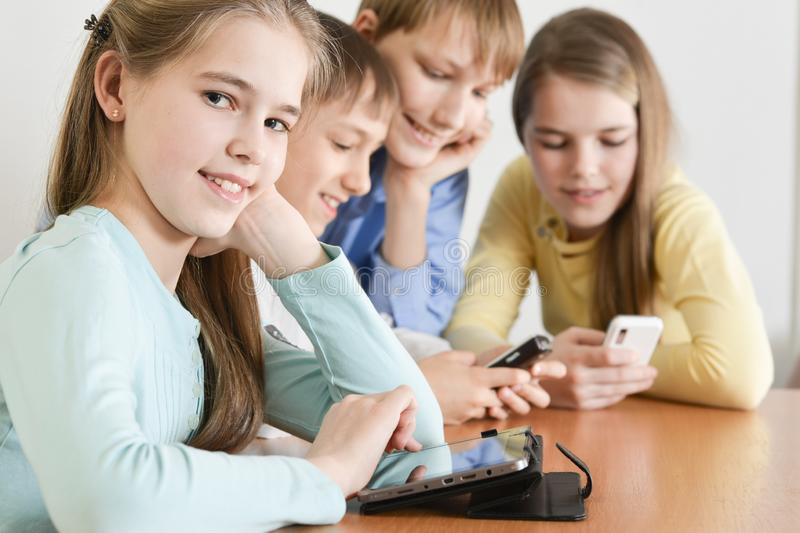 Funny boys and girls using digital devices together. At the table at home stock image