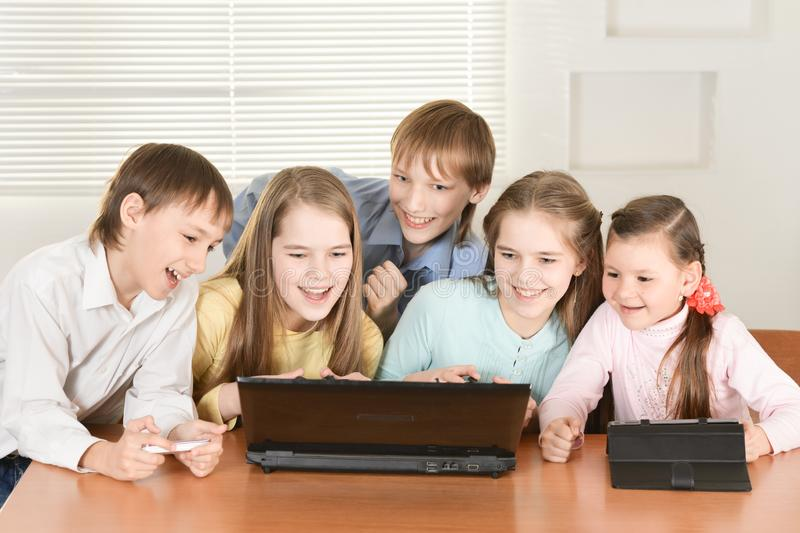 Funny boys and girls using digital devices together. At the table at home stock photo