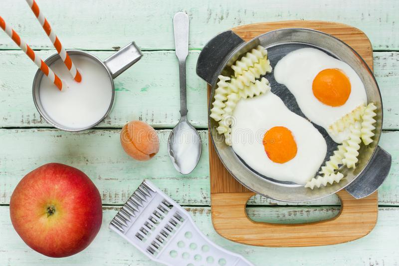 Funny breakfast idea - deceptive fried eggs and french fries fro. M yoghurt cream and fruit stock image