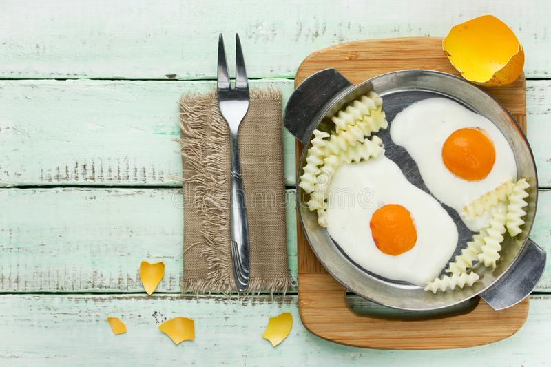 Funny breakfast idea - deceptive fried eggs and french fries fro. M yoghurt cream and fruit slices stock images