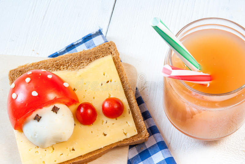 Funny breakfast for kid. Cute breakfast for kid: a sandwich with a funny cartoon mushroom with cheese, eggs and tomatoes stock photo