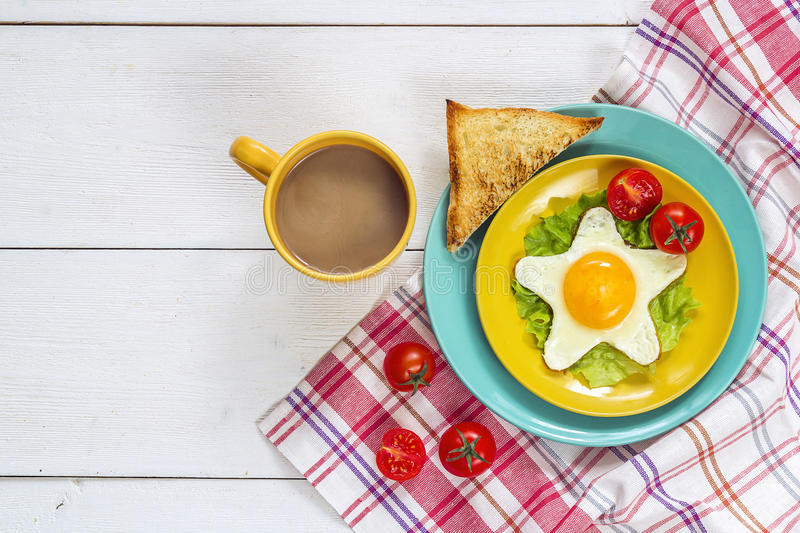 Funny Breakfast with star-shaped fried egg, toast, cherry tomato. Lettuce on colored plates and coffee. Top view stock photo