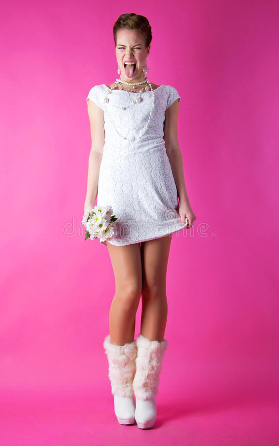 Funny bride. Full length portrait of naughty young funny girl bride wearing white dress and high heel boots, holding her dress and bunch of flowers, making funny stock images