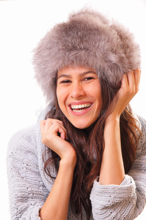 Funny brunette woman in a fur hat. Funny and beautiful brunette woman in a fur hat stock photography