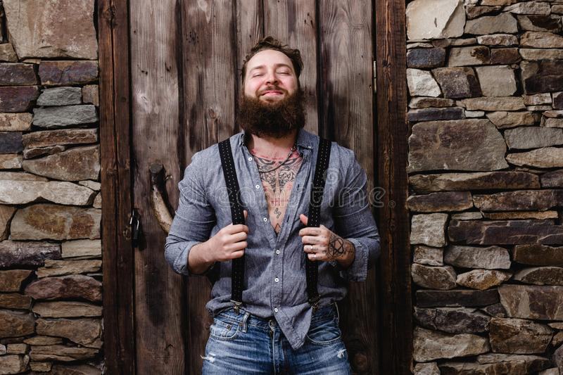 Funny brutal man with a beard and tattoos on his hands dressed in stylish casual clothes poses on the background of royalty free stock photo