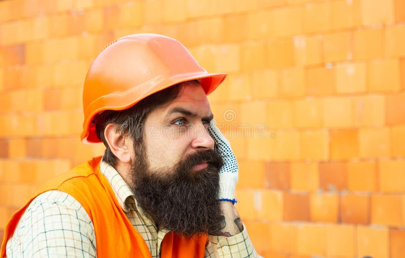 Funny builder. A man in a helmet thinks about life. Break in the construction. Sad bearded worker on brick wall royalty free stock images