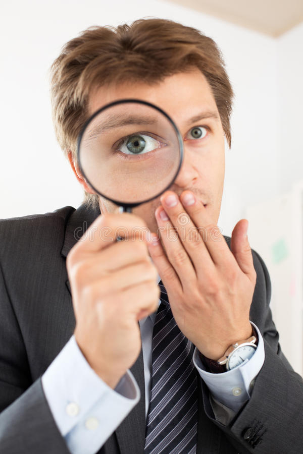 Funny business man holding magnifying glass royalty free stock photo