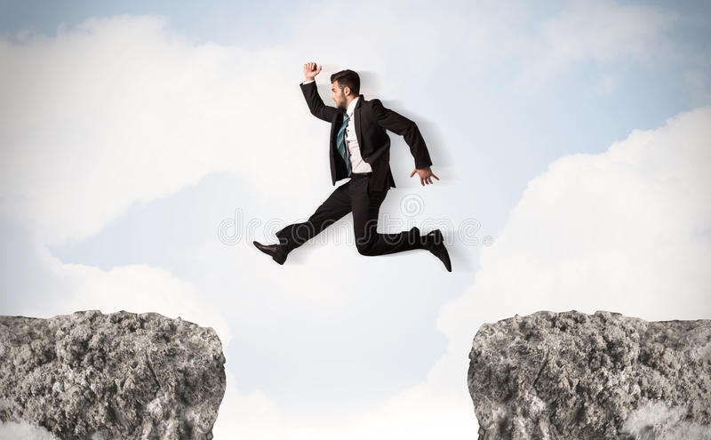 Funny business man jumping over rocks with gap stock photo for Jump the gap