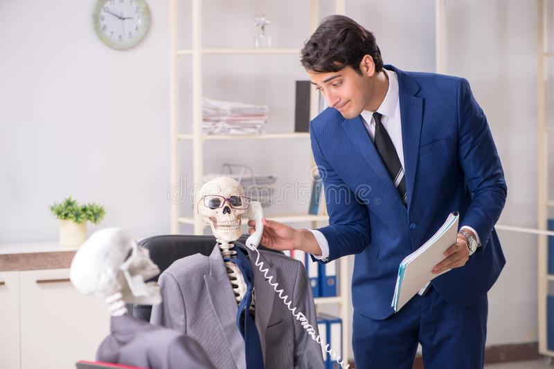 The funny business meeting with boss and skeletons. Funny business meeting with boss and skeletons royalty free stock images