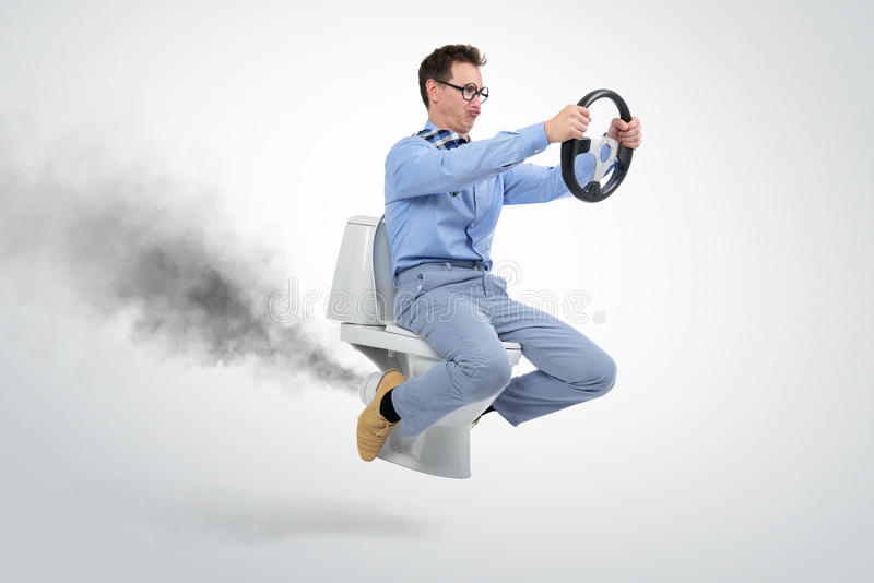Funny businessman flying on the toilet. On background stock image