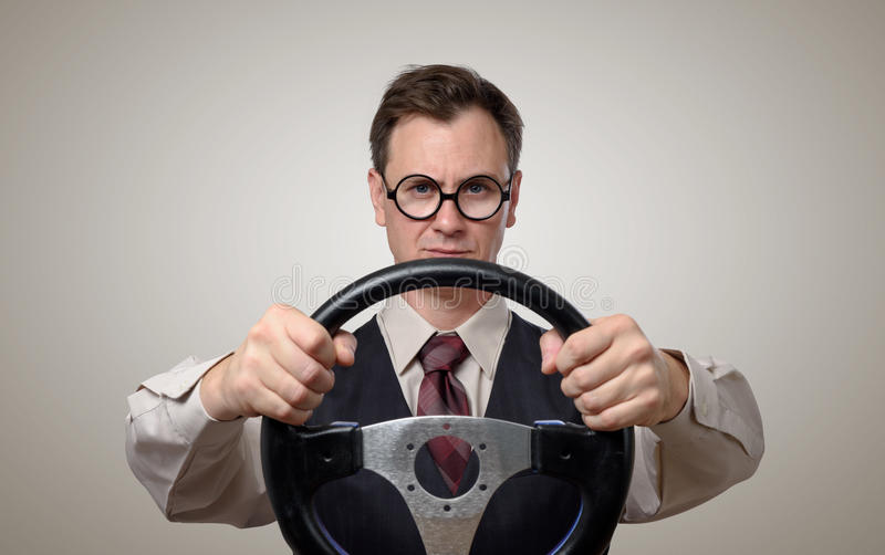 Funny businessman in glasses with a steering wheel. Car drive concept stock photos