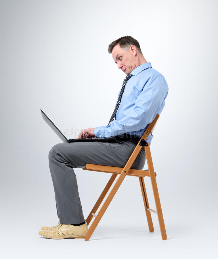 Funny businessman with a laptop sitting in a chair on background royalty free stock images