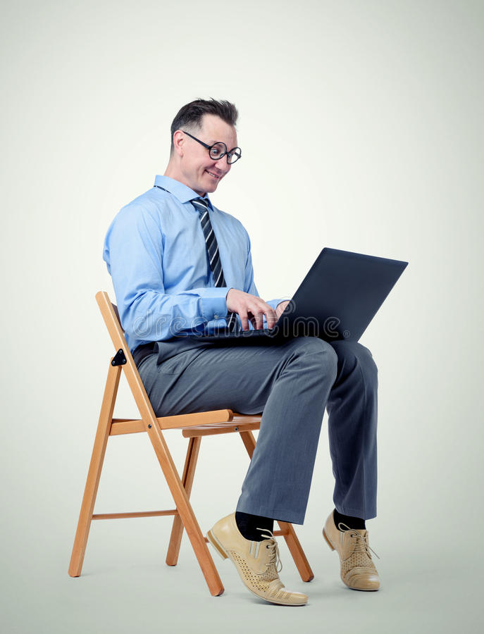 Funny businessman with a laptop sitting in a chair on background stock photo