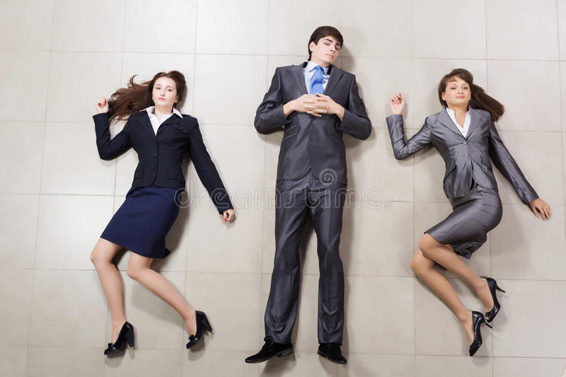 Funny businesspeople. Young people in business suits lying on floor stock photos