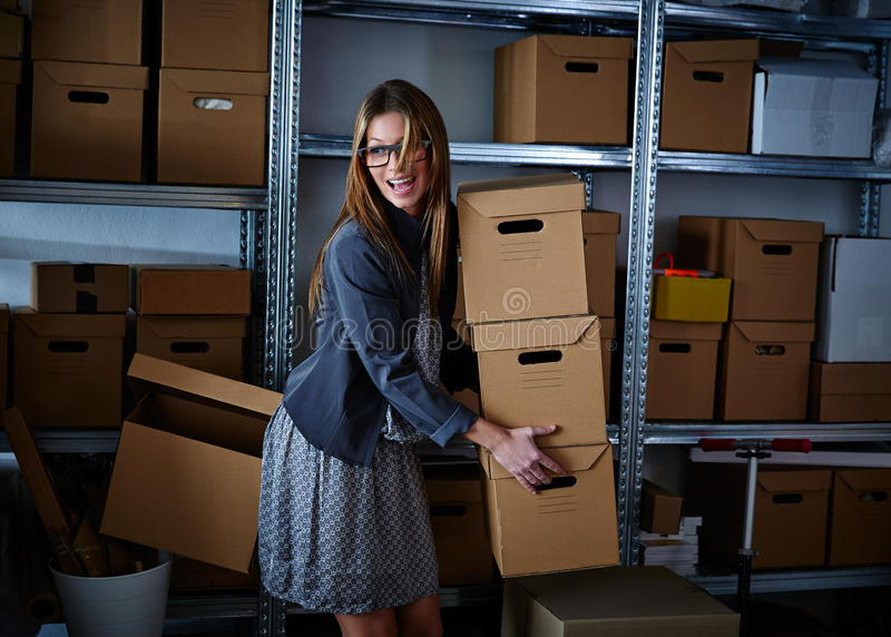 Funny businesswoman holding storage boxes. Funny businesswoman holding many storage boxes in office warehouse rack royalty free stock images
