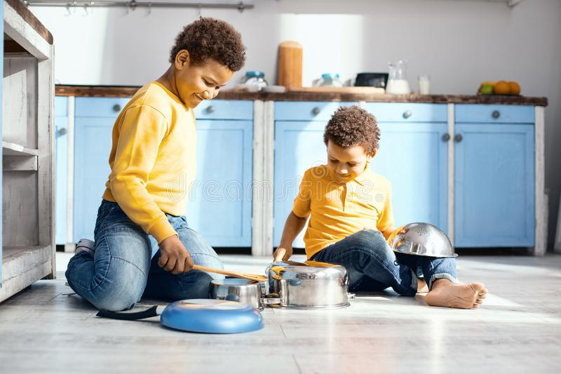 Cheerful little kids drumming on saucepans in kitchen royalty free stock images
