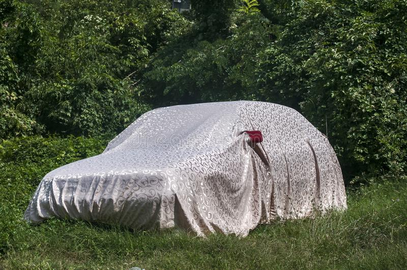 Funny car cover. Car funny covered on green grass house backyard stock photos