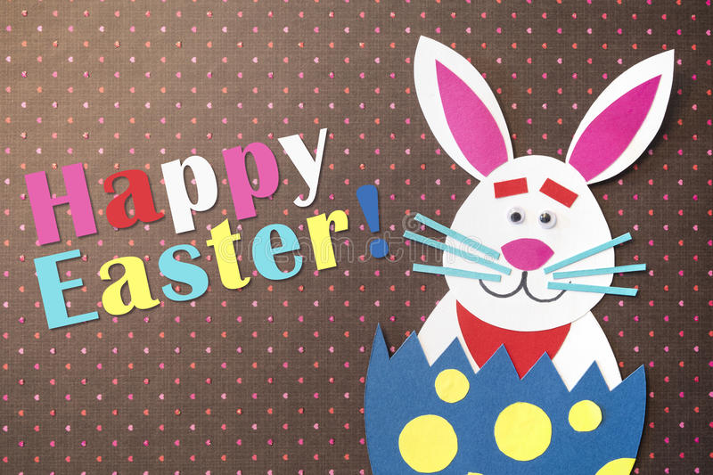 Funny cartoon rabbit placed inside eggs and handmade with colorful cardboard, greeting Easter holidays stock photography
