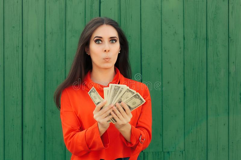 Funny Casual Girl Holding Money Thinking to Invest. Successful woman with lots of cash from lucky win royalty free stock photography