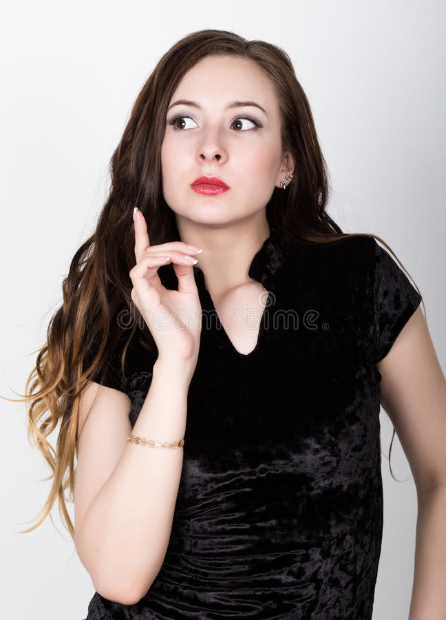 Funny casual smiling beautiful woman she raised her index finger up, pensive gesture. different happy emotions.  royalty free stock photography