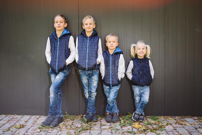 Funny Caucasian big family of three brothers and sister posing standing on growth background of wall in full growth. Equally royalty free stock images