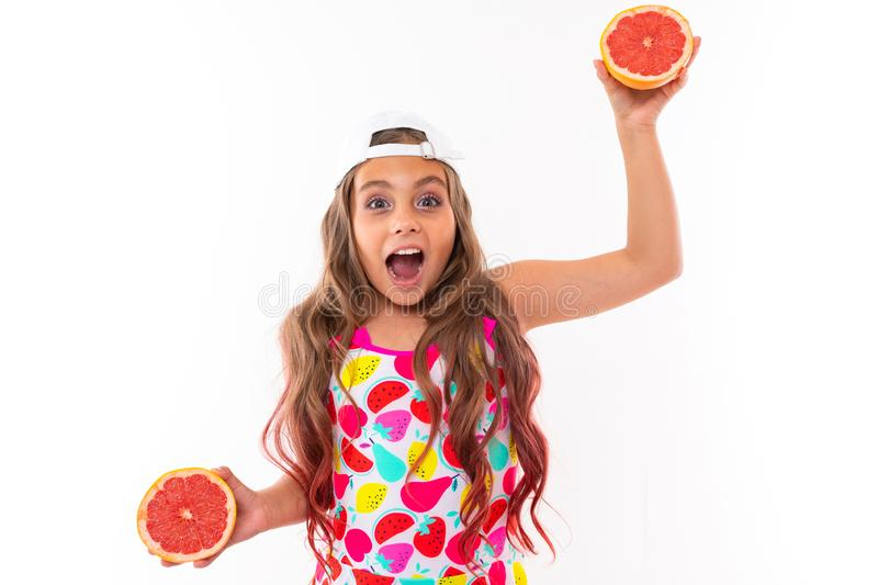 A funny caucasian girl with long hair, swimsuit, white cap holds grapefruit halves and smiles stock images