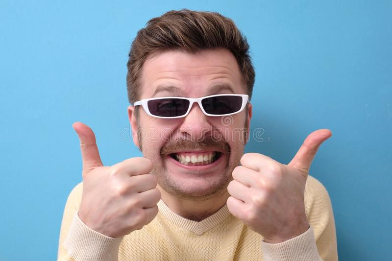 Funny caucasian man with retro mustache and sunglasses giving a thumbs up royalty free stock image
