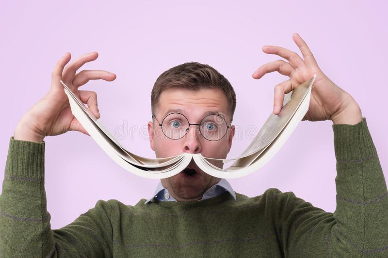 Funny caucasian male student in glasses holding book like a mustache royalty free stock photography