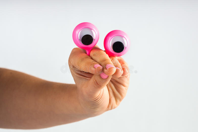 funny character creature looking puzzled and contemplating, depicted with female hand and googly eyes. Isolated on white with cop royalty free stock photos