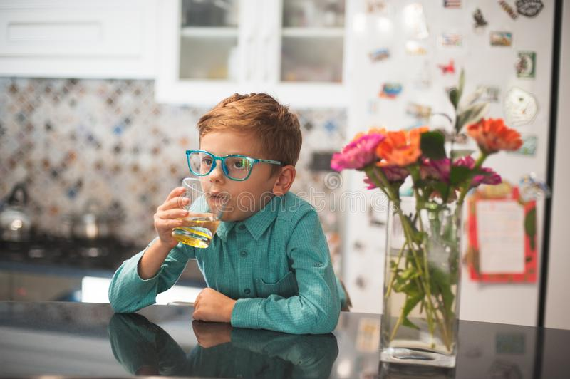 Funny charismatic retro style little boy in glasses drinking lemonade in kitchen. Thinking royalty free stock photo