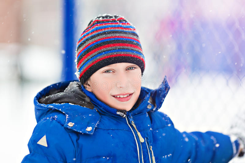 Funny cheerful boy in jacket and hat playing outdoors in winter stock image
