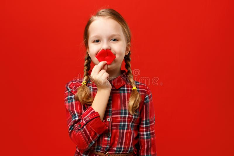 Funny cheerful little girl makes artificial fake lips on a red background. Child fooling around royalty free stock image