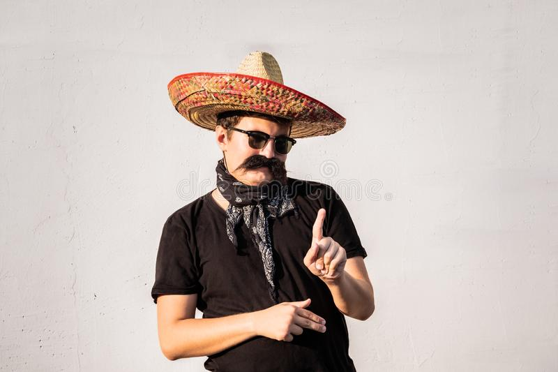 Funny and cheerful man dressed up in traditional mexican sombrero, false moustache, bandana and sunglasses. Humorous festive or h royalty free stock images