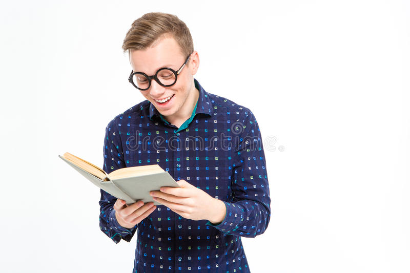 Funny cheerful smart blond man reading a book and smiling stock photos
