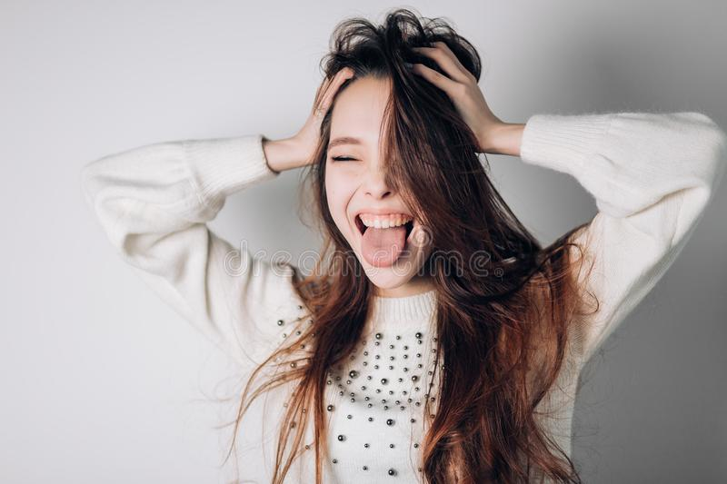 Funny cheerful woman shows tongue with eyes closed, shouting, fooling around, making a grimace. Positive emotions. Funny cheerful woman shows tongue with eyes stock photography