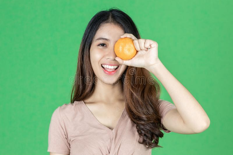 Funny cheerful young Asian woman holding two oranges on her eyes over green isolated background stock images