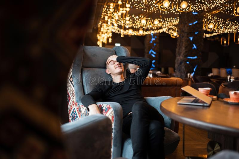 Funny cheerful young man in a stylish black shirt in trendy jeans sits at a vintage wooden table on a chair in a cafe royalty free stock photos