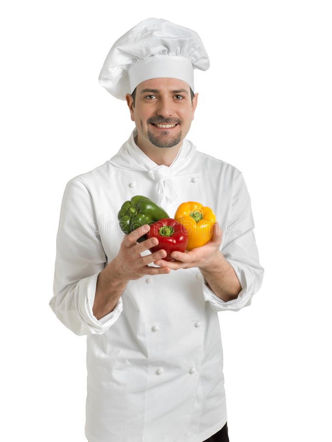 Chef holding peppers. A portrait of a smiling chef holding colorful peppers royalty free stock images